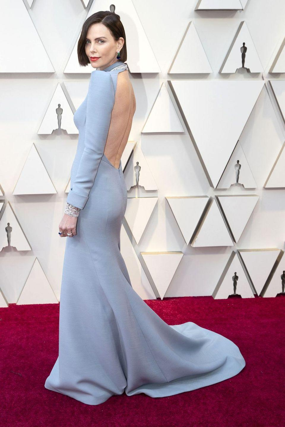 """<p>Charlize Theron stepped out in a <a href=""""https://www.harpersbazaar.com/beauty/hair/a26501330/charlize-theron-oscars-2019/"""" rel=""""nofollow noopener"""" target=""""_blank"""" data-ylk=""""slk:freshly chopped dark bob"""" class=""""link rapid-noclick-resp"""">freshly chopped dark bob</a> and a backless, dusty blue long-sleeved Dior gown. She accessorized the look with BVLGARI's Serpenti collection, including a white gold double necklace with a matching bracelet, and a diamond necklace of over 75 carats. Bling, bling.</p>"""