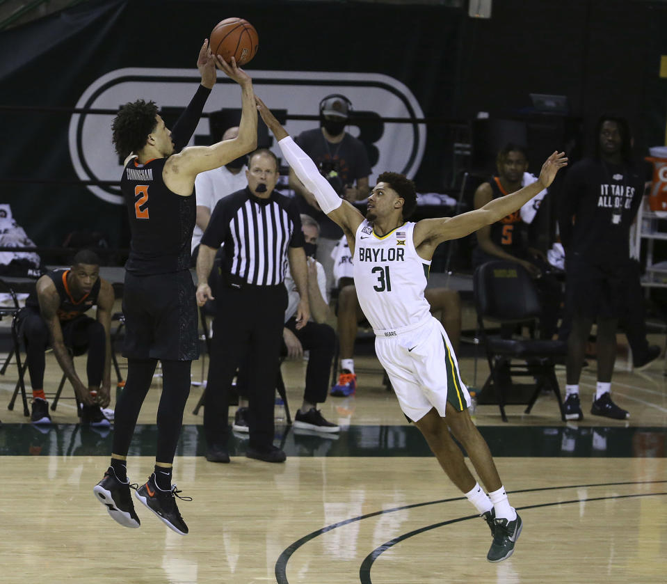 Oklahoma State guard Cade Cunningham (2) shoots a three point shot over Baylor guard MaCio Teague (31) in the second half of an NCAA college basketball game, Thursday, March 4, 2021, in Waco, Texas. (AP Photo/Jerry Larson)