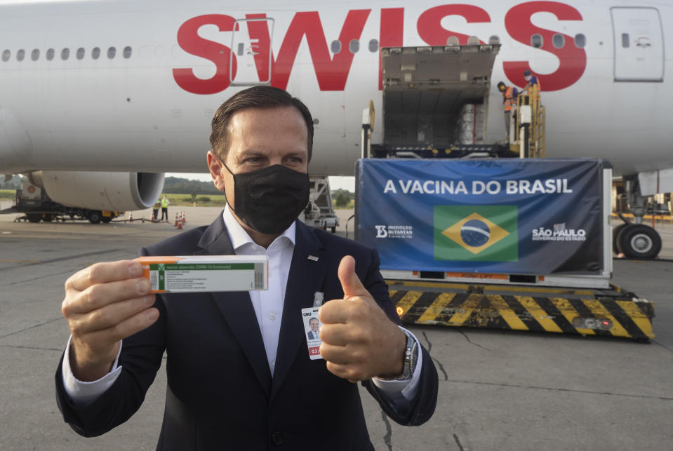 Sao Paulo Gov. Joao Doria poses for photo flashing a thumbs up next to a container carrying the experimental COVID-19 vaccine CoronaVac after it was unloaded from a cargo plane that arrived from China at Guarulhos International Airport in Guarulhos, near Sao Paulo, Brazil, Thursday, Dec. 3, 2020. (AP Photo/Andre Penner)