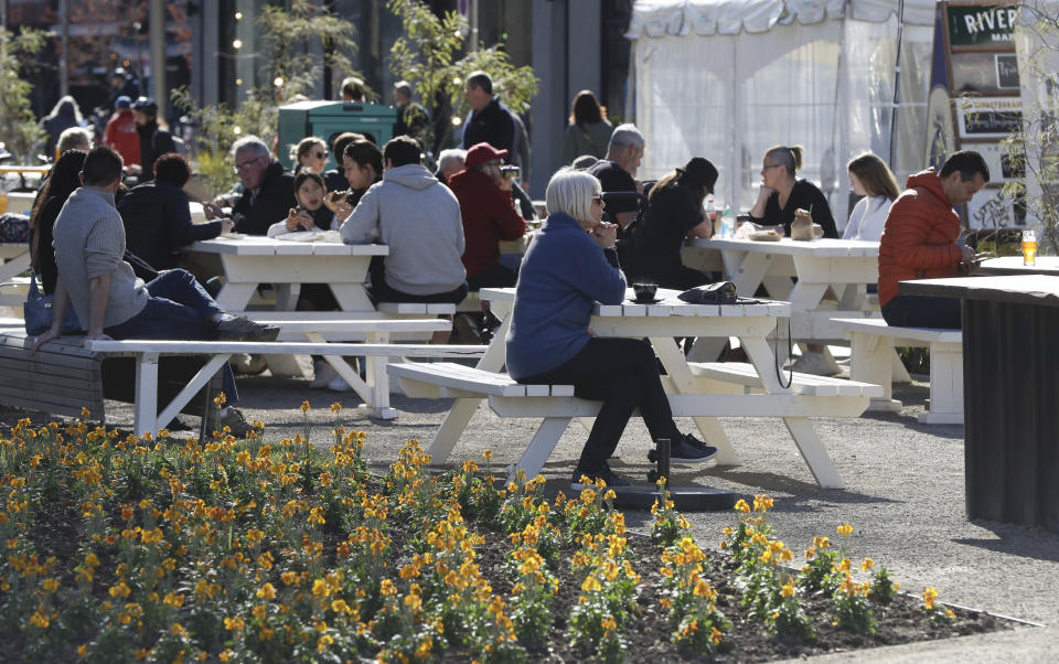 Customers enjoy lunch in the sunshine at the Riverside Market in Christchurch, New Zealand, Sunday, Aug. 9, 2020. New Zealand marked a 100 days of being free from the coronavirus in its communities Sunday, Aug. 9, with just a handful of infections continuing to be picked up at the border where people are quarantined. (AP Photo/Mark Baker)