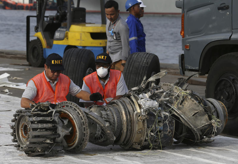 FILE - In this Nov. 4, 2018, file photo officials inspect an engine recovered from the crashed Lion Air jet in Jakarta, Indonesia. On the anniversary of the first crash of a Boeing 737 Max, the CEO will begin two days of testimony before Congress by telling lawmakers that the aircraft company knows it made mistakes and is throwing everything into fixing the plane. (AP Photo/Achmad Ibrahim, File)