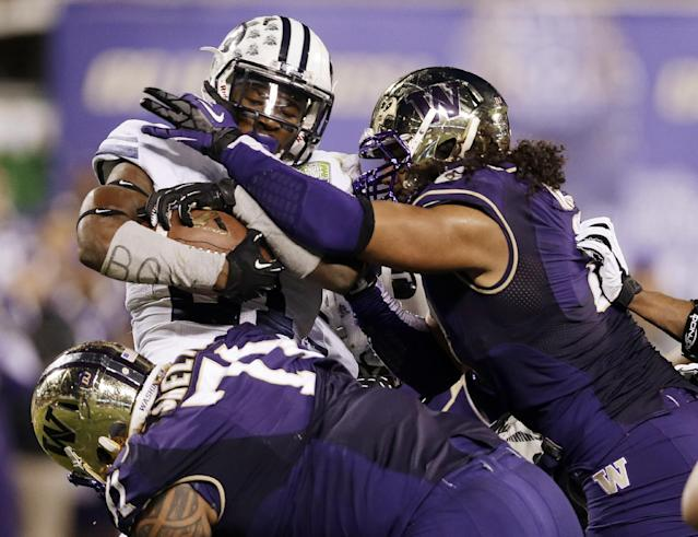 BYU running back Jamaal Williams, left, is tackled by Washington's Hau'oli Kikaha, right, and Danny Shelton, bottom, during the first half of the Fight Hunger Bowl NCAA college football game, Friday, Dec. 27, 2013, in San Francisco. (AP Photo/Marcio Jose Sanchez)