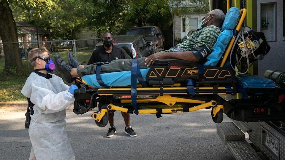 EMS medics transport a man with possible Covid-19 symptoms to the hospital on August 07, 2020 in Austin, Texas. Nationwide the African American community continues to be disproportionally affected by the coronavirus pandemic. Austin-Travis County EMS has seen the number of new hospitalizations decrease, even as Covid-19 deaths continue. (Photo by John Moore/Getty Images)