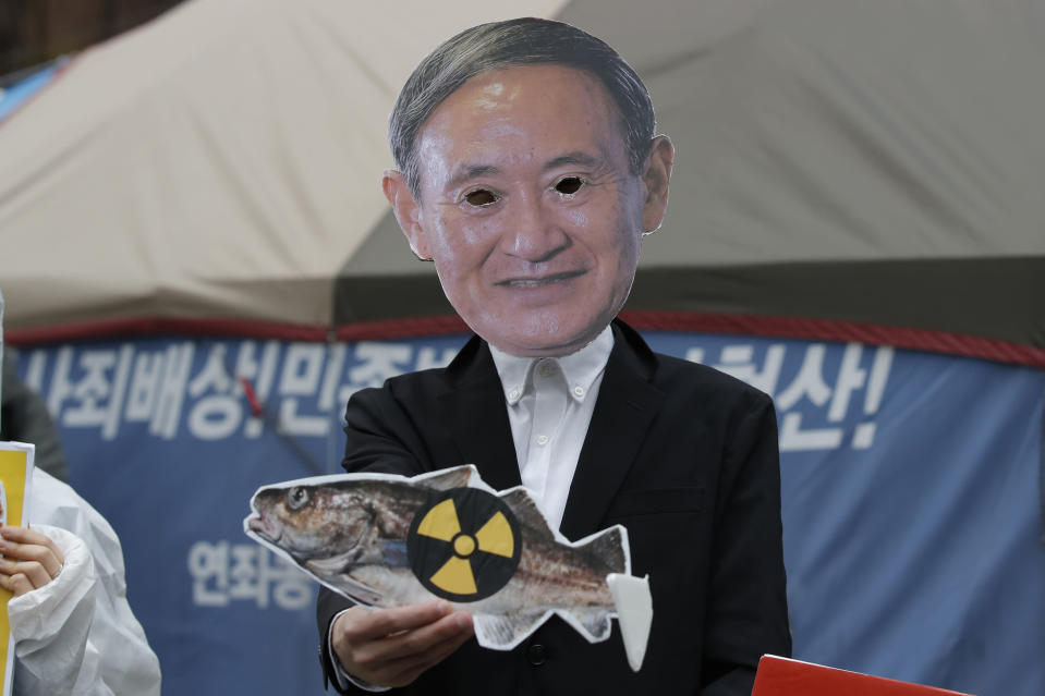 An environmental activist wearing a mask of Japanese Prime Minister Yoshihide Suga performs to denounce the Japanese government's decision near the Japanese embassy in Seoul, South Korea, Tuesday, April 13, 2021. Japan's government decided Tuesday to start releasing massive amounts of treated radioactive water from the wrecked Fukushima nuclear plant into the Pacific Ocean in two years - an option fiercely opposed by local fishermen and residents. (AP Photo/Lee Jin-man)