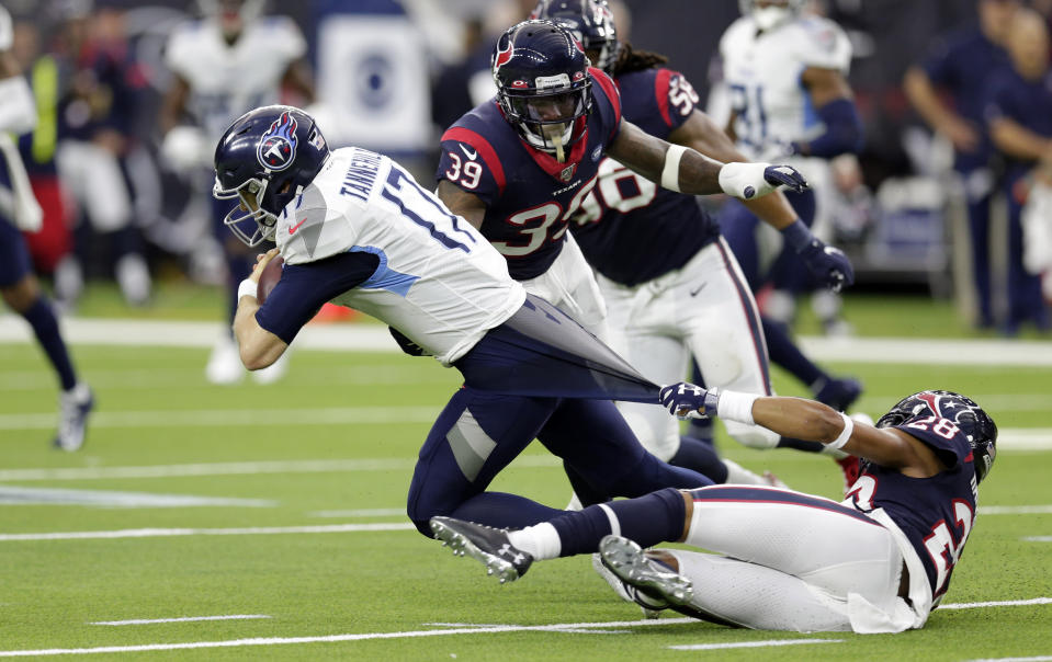 Houston Texans cornerback Vernon Hargreaves III (28) grabs the shirt of Tennessee Titans quarterback Ryan Tannehill (17) as he tries to tackle him during the first half of an NFL football game Sunday, Dec. 29, 2019, in Houston. (AP Photo/Michael Wyke)