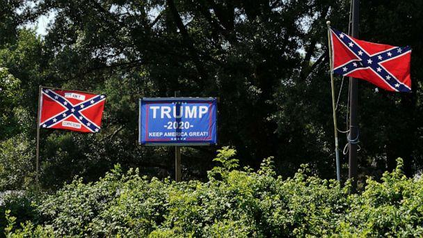 PHOTO: A campaign sign for U.S. President Donald Trump sits between two Confederate flags, one bearing the words 'I ain't coming down' in the backyard of a home in Sandston, Va., July 4, 2020. (Kevin Lamarque/Reuters)