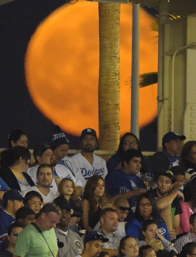 A supermoon rises behind fans during a baseball game between the Los Angeles Dodgers and the San Diego Padres at Dodger Stadium, Saturday, July 12, 2014, in Los Angeles. (AP Photo/Mark J. Terrill)
