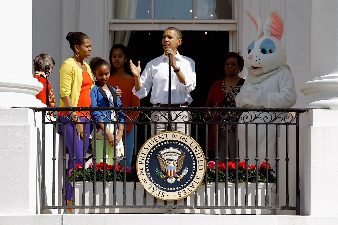 U.S. President Barack Obama (C) speaks to participants along with (L-R) first lady Michelle Obama, and daughters Sasha and Malia during the White House Easter Egg Roll on the South Lawn of the White House on April 9, 2012 in Washington, DC. Thousands of people people are expected to attend the 134-year-old tradition of rolling colored eggs down the White House lawn that was started by President Rutherford B. Hayes in 1878.  (Photo by Chip Somodevilla/Getty Images)