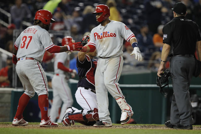Philadelphia Phillies' Carlos Santana, center, celebrates a two-run home run with teammate Odubel Herrera (37), who also scored, in the sixth inning of a baseball game against the Washington Nationals at Nationals Park, Friday, June 22, 2018, in Washington. (AP Photo/Carolyn Kaster)