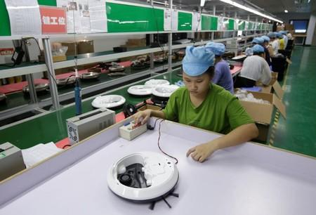 An employee works on the production line of a robot vacuum cleaner at a factory of Matsutek in Shenzhen