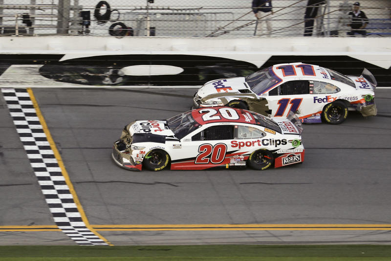 Erik Jones (20) heads to the finish line to win the NASCAR Busch Clash auto race at Daytona International Speedway, Sunday, Feb. 9, 2020, in Daytona Beach, Fla. Denny Hamlin (11), who was a lap down, helped Jones with a push in Turn 4. (AP Photo/John Raoux)