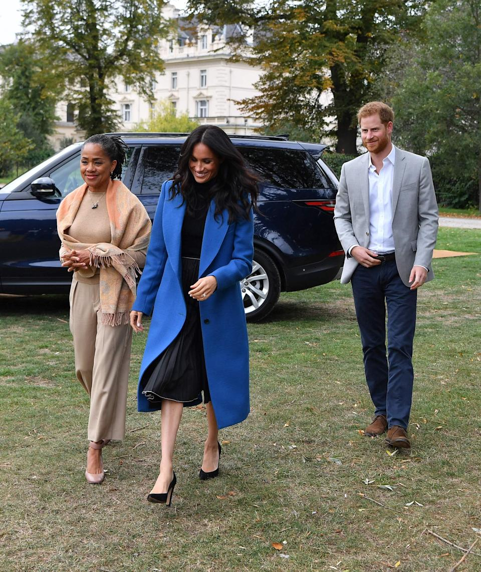 <p>On September 20, the Duchess of Sussex was joined by her mother Doria Ragland and Prince Harry to celebrate the launch of her new cookbook. For the Kensington Palace event, the royal dressed in a cobalt blue Smyth coat, Tuxe body and a pleated skirt by Misha Nonoo. To accessorise the outfit, the Duchess added a pair of Sarah Flint heels. <em>[Photo: Getty]</em> </p>