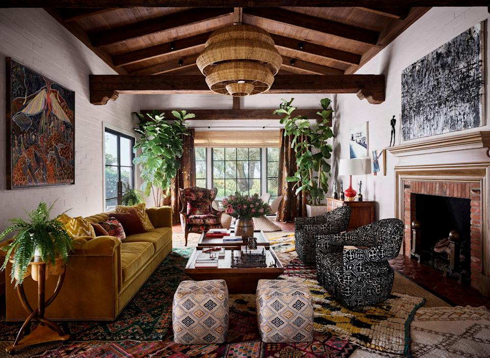 The voluminous living room is anchored by a collage of Moroccan rugs set atop a massive sisal carpet. The painting above the fireplace is by Hooper Dunbar. On the opposite wall is a painting by Frantz Zephirin.