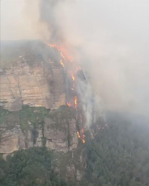 A fire burns at the side of a cliff in Blue Mountains