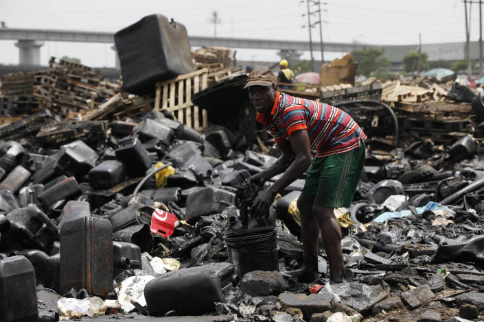 In this image taken Thursday Feb. 28, 203 a man salvages engine oil from demolished houses at Ijora Badia slum in Lagos, Nigeria. The bulldozers arrived at dawn to this neighborhood of shanty homes and concrete buildings in Nigeria's largest city, followed by police officers in riot gear carrying Kalashnikov assault rifles. The police banged on doors, corralling the thousands who live in Ijora-Badia off to the side as the bulldozers' blades tore through scrap-lumber walls, its track grinding the possessions inside into the black murk of swamp beneath it. It left behind only a field of debris that children days later picked through, their small hands dodging exposed rusty nails to pull away anything of value left behind. (AP Photo/Sunday Alamba)