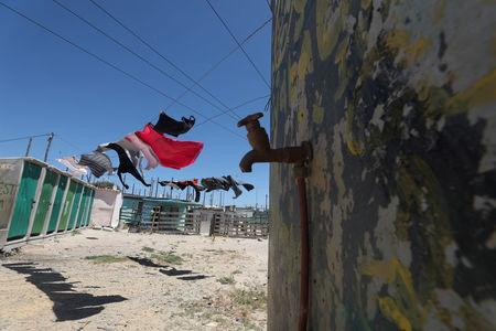 """Clothing hangs above a communal tap in Khayelitsha township, near Cape Town, South Africa, December 12, 2017. The city has imposed severe restrictions in an attempt to avert """"Day Zero"""", the point at which the dams run dry or have levels too low to use for potable water. Despite some winter rainfall dams are running dangerously low following the worst drought in a century in the region. REUTERS/Mike Hutchings"""