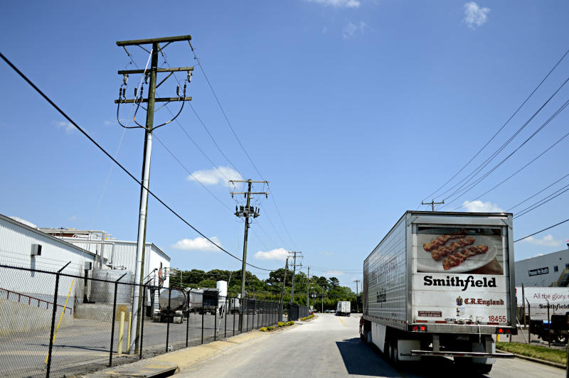 In this May 29, 2013 photo, a truck waits outside the gates of Smithfield Foods in Smithfield, Va. Smithfield Foods has agreed to be bought by Shuanghui International Holdings for about $4.72 billion. Residents in the southeastern Virginia town have mixed reactions to the idea that the maker of their famous cured hams may soon be owned by a Chinese company. (AP Photo/The Virginian-Pilot, Amanda Lucier)