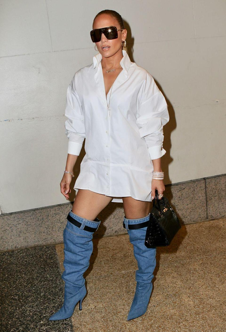<p>J.Lo is seen in New York City wearing an oversize button-down shirt, a mini Birkin bag, and standout thigh-high denim boots. Her shoes even have their own belts! </p>