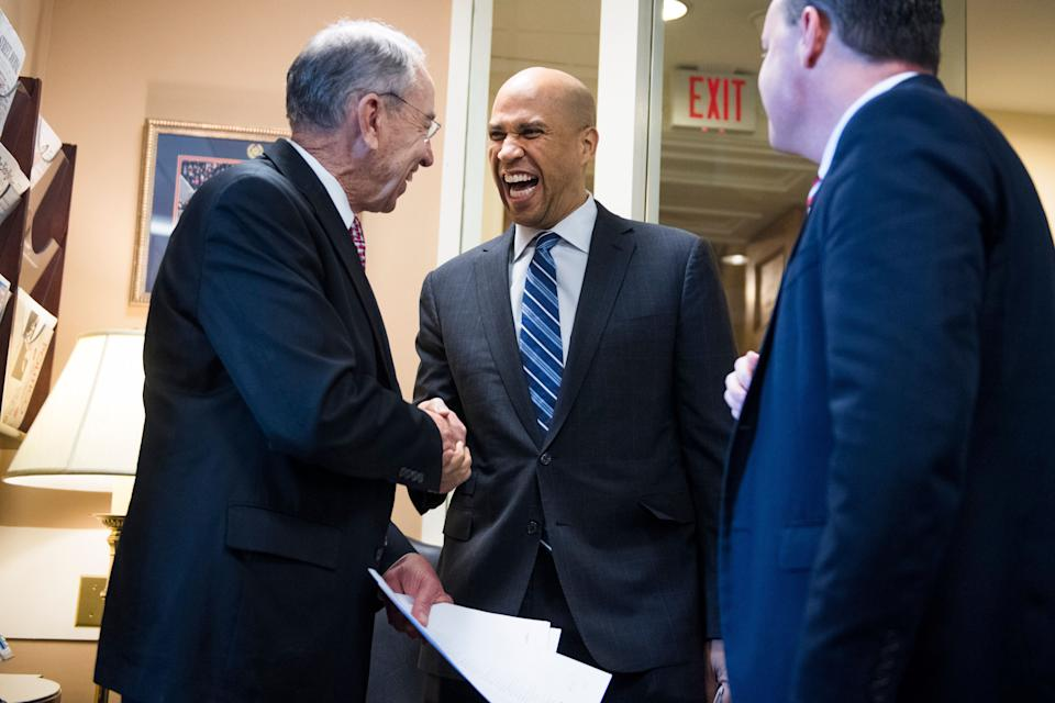 Sen. Cory Booker (D-N.J.) congratulates Republican Sens. Chuck Grassley (Iowa), left, and Mike Lee (Utah) on passage of the First Step Act. (Photo: Tom Williams via Getty Images)