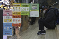 """Posters on precautions against the coronavirus are displayed at a subway station in Seoul, South Korea, Tuesday, Nov. 24, 2020. The signs on posters read """"Precautions against the coronavirus and please wear a mask."""" (AP Photo/Ahn Young-joon)"""