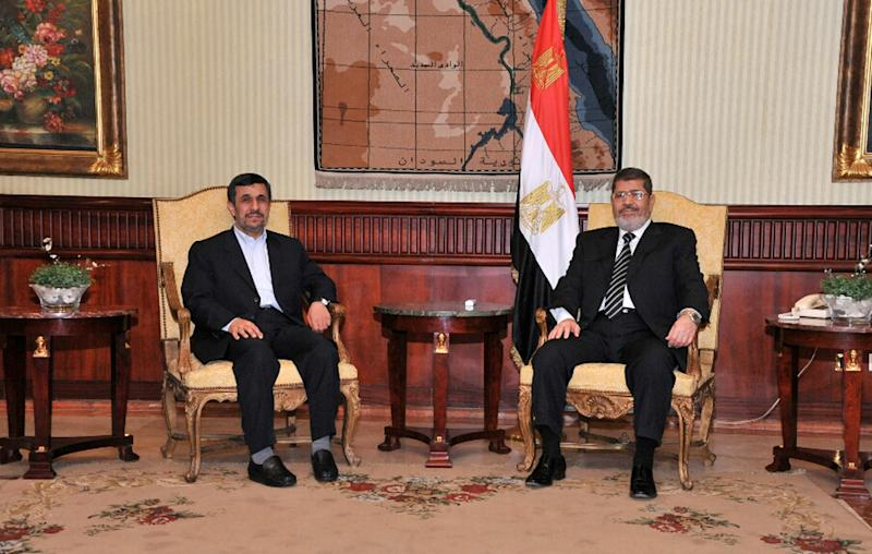 In this image released by the Egyptian Presidency, Iran's President Mahmoud Ahmadinejad, left, and Egyptian President Mohammed Morsi, right, pose for photographers in Cairo, Egypt, Tuesday, Feb. 5, 2013. Ahmadinejad arrived in Cairo on Tuesday for the first visit by an Iranian leader in more than three decades, marking a historic departure from years of frigid ties between the two regional heavyweights.(AP Photo/Egyptian Presidency)