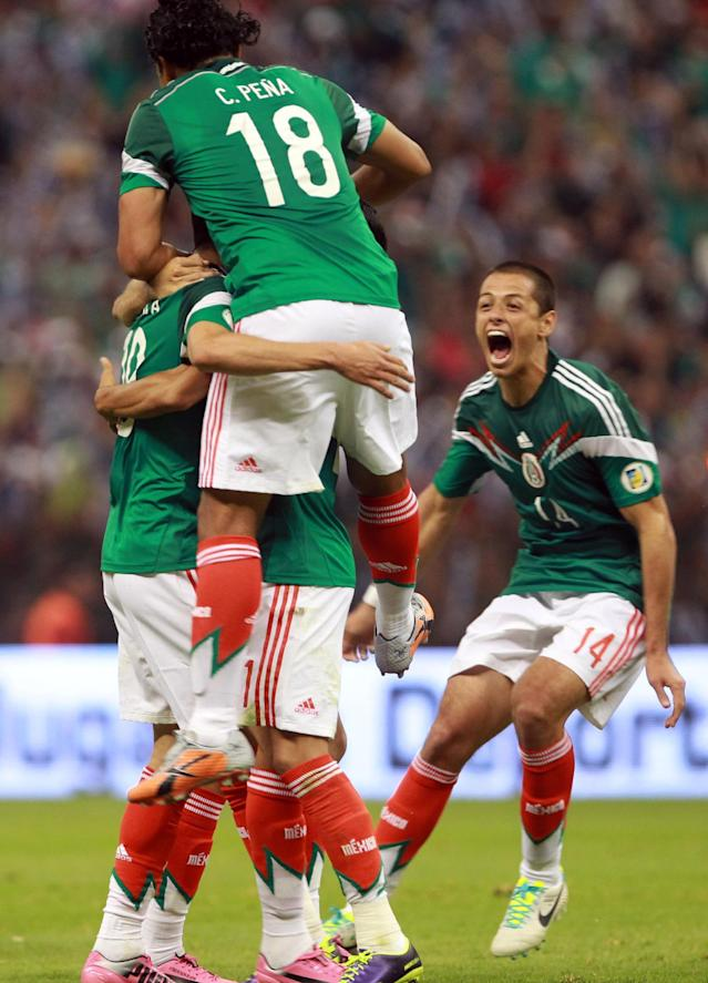Mexico's Oribe Peralta, obscured at left, celebrates with teammates Carlos Pena (18) and Javier Hernandez, right, after scoring against Panama during a 2014 World Cup qualifying match in Mexico City, Friday, Oct. 11, 2013. (AP Photo/Christian Palma)