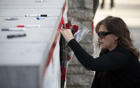 A woman signs a memorial card for the victims near the scene on Yonge St - Credit: Cole Burston/Getty Images