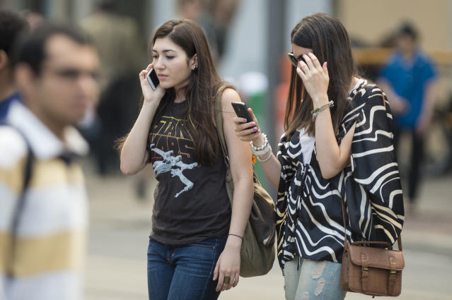 Two women use their cellphone while walking on Yonge Street in Toronto. (Carlos Osorio/Toronto Star via Getty Images)