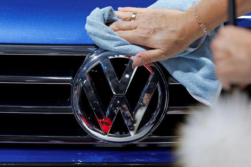 A worker shines the grill of a Volkswagen car displayed on media day at the Paris auto show, in Paris