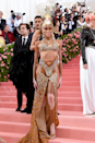 """<p>Can we take a moment to appreciate how extra Winnie Harlow's <a href=""""https://www.cosmopolitan.com/uk/fashion/celebrity/g27383773/met-gala-2019-naked-dresses/"""" rel=""""nofollow noopener"""" target=""""_blank"""" data-ylk=""""slk:2019 Met Gala"""" class=""""link rapid-noclick-resp"""">2019 Met Gala</a> carnival queen-inspired Tommy Hilfiger dress was? The headpiece is the icing on the cake.</p>"""