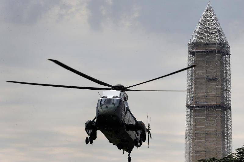 In this photo taken May 28, 2013, repairs continue on the Washington Monument as Marine One helicopter comes in for a landing on the South Lawn of the White House in Washington. While the Monument's earthquake damage is being repaired over the next year, 488 lamps will restore the tower's glow each night on the National Mall starting Monday, July 8, 2013. (AP Photo/Charles Dharapak)