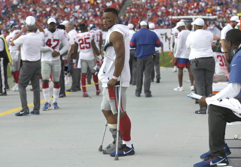 New York Giants running back Saquon Barkley stands on crutches in the bench area after getting injured against the Tampa Bay Buccaneers during the first half of an NFL football game Sunday, Sept. 22, 2019, in Tampa, Fla. (AP Photo/Jason Behnken)