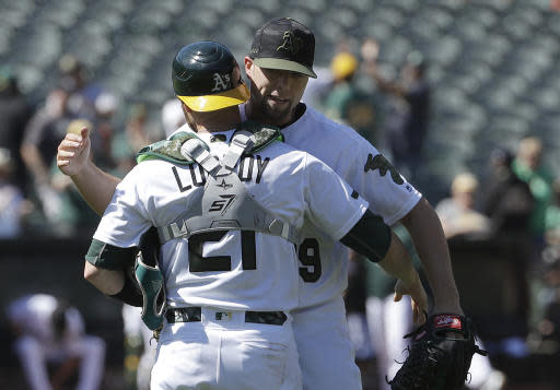 Oakland Athletics catcher Jonathan Lucroy, left, celebrates with pitcher Blake Treinen after they defeated the Arizona Diamondbacks in a baseball game in Oakland, Calif., Sunday, May 27, 2018. (AP Photo/Jeff Chiu)