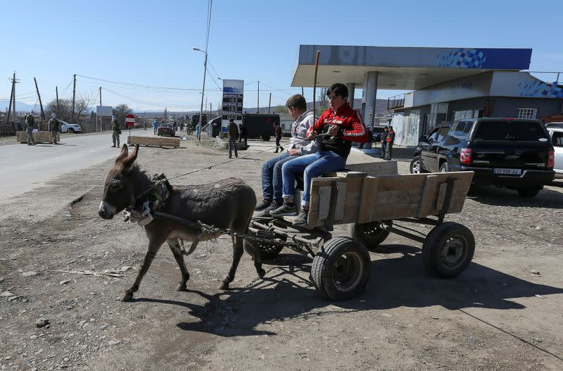 FILE PHOTO: Boys sit on a donkey-drawn cart near a check point in Marneuli