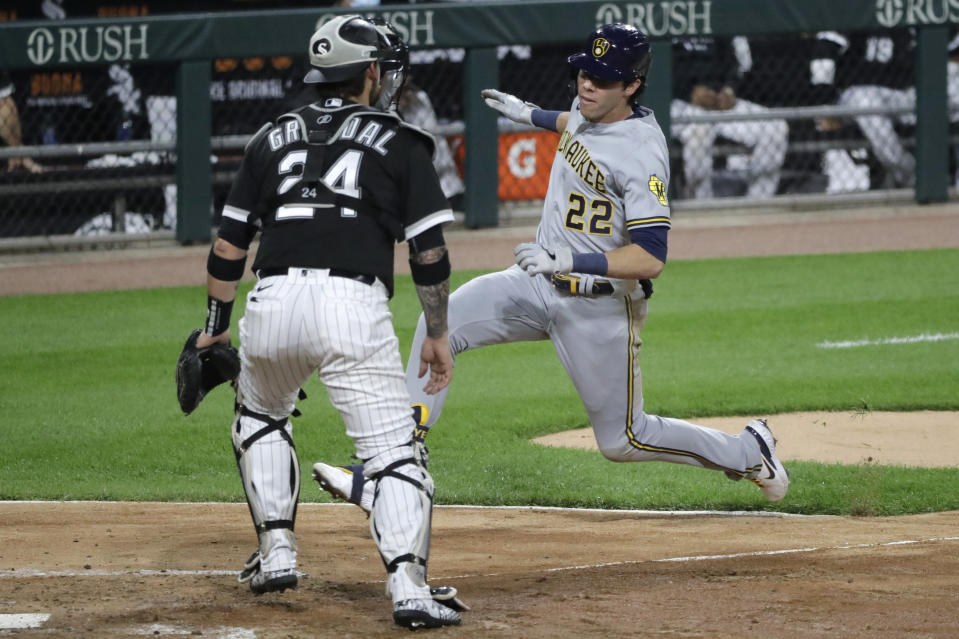 Milwaukee Brewers' Christian Yelich, right, scores on his inside-the-park home run against Chicago White Sox catcher Yasmani Grandal during the fifth inning of a baseball game in Chicago, Thursday, Aug. 6, 2020. (AP Photo/Nam Y. Huh)