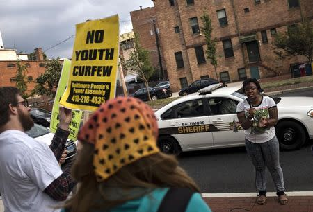 Protesters demonstrate before a community meeting with city officials about new youth curfew legislation going into effect on August 8 at the University of Baltimore Law Center in Baltimore Tuesday July 29, 2014. REUTERS/James Lawler Duggan