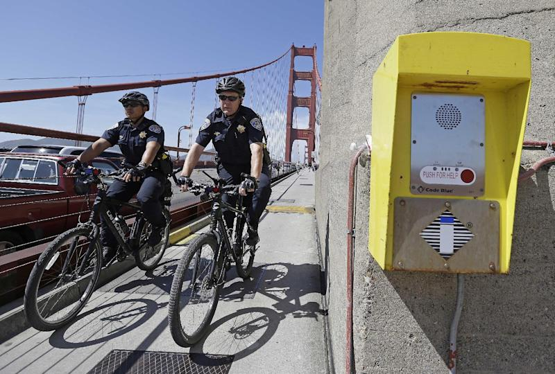 In this photo taken Tuesday, April 30, 2013 California Highway Patrol officers Steve Bautista, left, and Sandro Salvetti, right, ride their bicycles past a crisis counseling call box during a patrol on the Golden Gate Bridge in San Francisco. About 1,500 people have plunged from the bridge, making it one of the world's favorite suicide spots. (AP Photo/Eric Risberg)