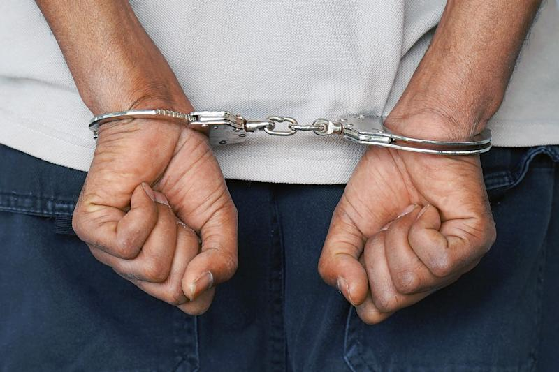 Close-up. Arrested man handcuffed hands at the back isolated on gray background. Prisoner or arrested terrorist, close-up of hands in handcuffs.