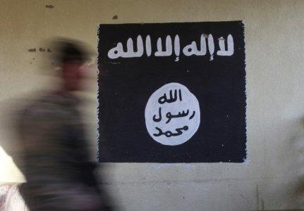 A member of the Iraqi rapid response forces walks past a wall painted with the black flag commonly used by Islamic State militants, at a hospital damaged by clashes during a battle between Iraqi forces and Islamic State militants in the Wahda district of eastern Mosul, Iraq, January 8, 2017. REUTERS/Alaa Al-Marjani