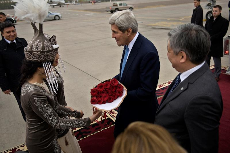 US Secretary of State John Kerry (C) is greeted upon his arrival at Manas International Airport in Bishkek on October 31, 2015 (AFP Photo/Brendan Smialowski)