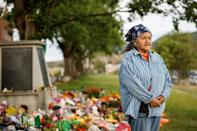 Kamloops Indian Residential School survivor Evelyn Camille, 82, poses next to a makeshift memorial at the former Kamloops Indian Residential School to honour the 215 children whose remains have been discovered buried near the facility