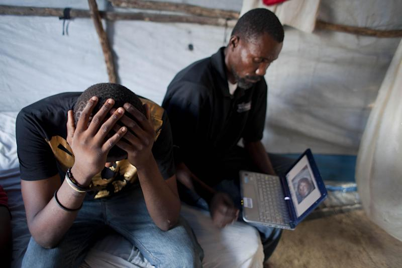 In this April 24, 2013 photo, Darlin Lexima, left, holds his head after seeing the body of Merius Civil on a computer, shown to him by camp leader Elie Joseph Jean-Louis inside Lexima's tent home at Camp Acra in Port-au-Prince, Haiti. Lexima, 21, was arrested by police while walking home from a disco club on the same early morning that Civil was arrested, on April 15 while residents at their camp were protesting a raid by motorcyclists who set fire to their homes. Civil's sister says her brother was taking out the trash when he was arrested. Lexima said he later saw Civil in police custody, too dazed to speak. The law firm of Patrice Florvilus, an attorney representing the dead man's family and other Camp Acra residents, said that it believes Civil died at the Delmas station, and that witnesses reported seeing officers carry a sheet-covered body from the station to a patrol car. (AP Photo/Dieu Nalio Chery)