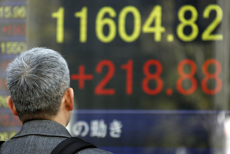 A man looks at an electronic stock board of a securities firm in Tokyo, Monday, Feb. 25, 2013. Japanese stocks led Asian markets higher Monday, jumping on a report that the prime minister's pick for the next central bank governor will be a strong advocate of loose monetary policy aimed at reviving the moribund economy.  (AP Photo/Koji Sasahara)