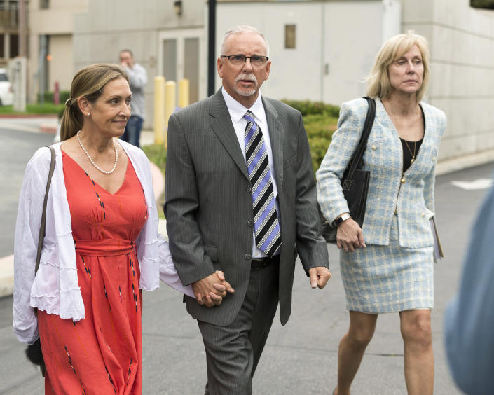 FILE - In this June 26, 2019, file photo, UCLA gynecologist Dr. James Heaps, center, his wife Deborah, left, and defense attorney Tracy Green leave Los Angeles Superior Court. Heaps, faces additional criminal charges in a case where he is accused of sexually abusing seven women, the Los Angeles Times reported Monday, May 24, 2021. Heaps was taken into custody Monday on $1.19 million bail after the grand jury's indictment was unsealed, the newspaper reported. He was arrested in June 2019; his medical license has been suspended by court order as that case moves forward. (AP Photo/Damian Dovarganes, File)