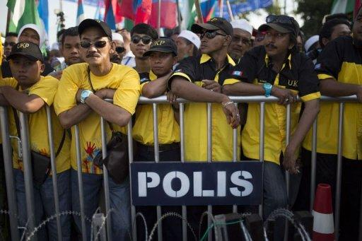 <p>Supporters wait behind a police fence as Malaysia's opposition leader Anwar Ibrahim (unseen) submits his election nomination in Berapit on April 20, 2013. Hundreds of cases of Malaysian election violence have been reported since campaigning for tightly contested May 5 polls got under way at the weekend, police were quoted saying on Wednesday.</p>