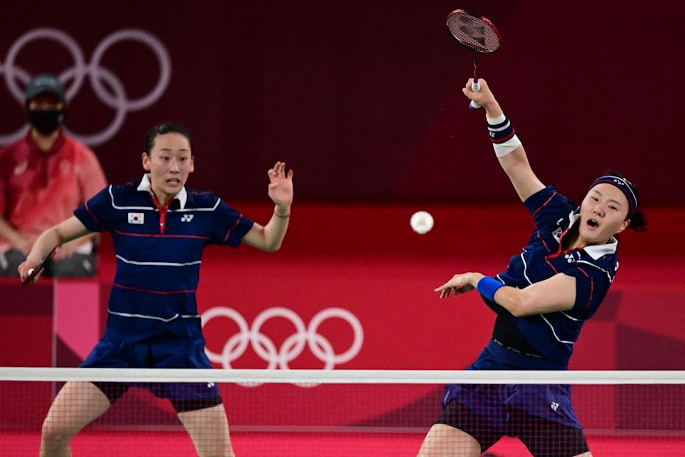 <p>South Korea's Shin Seung-chan (R) hits a shot next to South Korea's Lee So-hee in their women's doubles badminton semi-final match against Indonesia's Greysia Polii and Indonesia's Apriyani Rahayu during the Tokyo 2020 Olympic Games at the Musashino Forest Sports Plaza in Tokyo on July 31, 2021. (Photo by Pedro PARDO / AFP)</p>