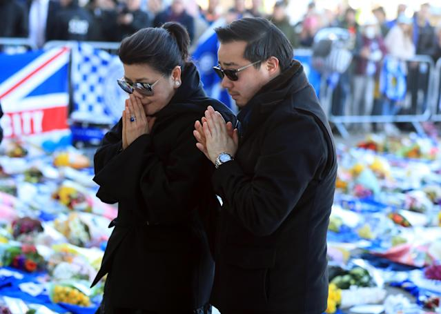 <p>Aiyawatt Srivaddhanaprabha lays a wreath in memory of his father with his mother Aimon. Mike Egerton/PA Wire </p>