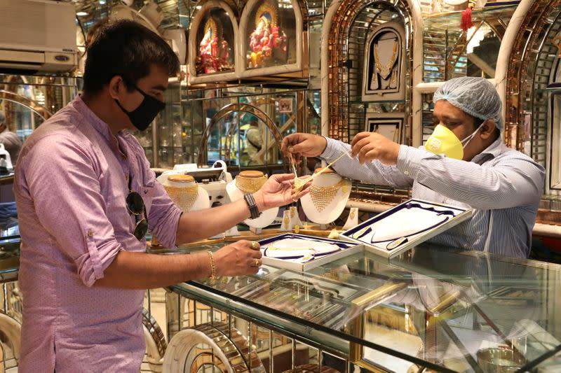 A salesman shows gold necklaces to a customer at a jewellery showroom, after authorities eased lockdown restrictions that were imposed to slow the spread of the coronavirus disease, in Kolkata