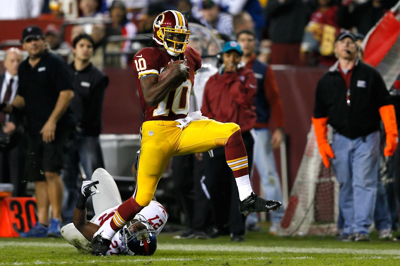 LANDOVER, MD - DECEMBER 03:  Quarterback Robert Griffin III #10 of the Washington Redskins runs for a 46-yard gain as he is taken down by  Stevie Brown #27 of the New York Giants in the second half at FedExField on December 3, 2012 in Landover, Maryland.  (Photo by Rob Carr/Getty Images)