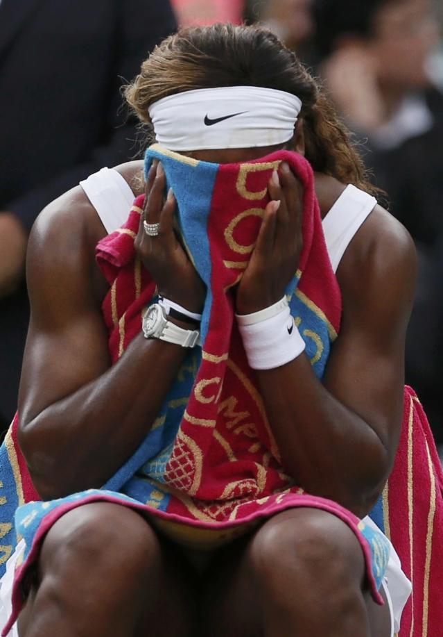 Serena Williams of the U.S. holds a towel to her face during a break in her women's singles tennis match against Alize Cornet of France at the Wimbledon Tennis Championships, in London June 28, 2014. REUTERS/Stefan Wermuth (BRITAIN - Tags: SPORT TENNIS)